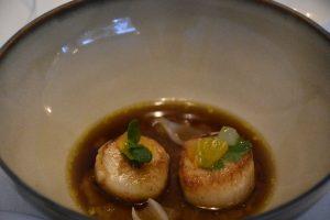 Vieira salteada con aceite de curry acompañada de nabo daikon y mandarina