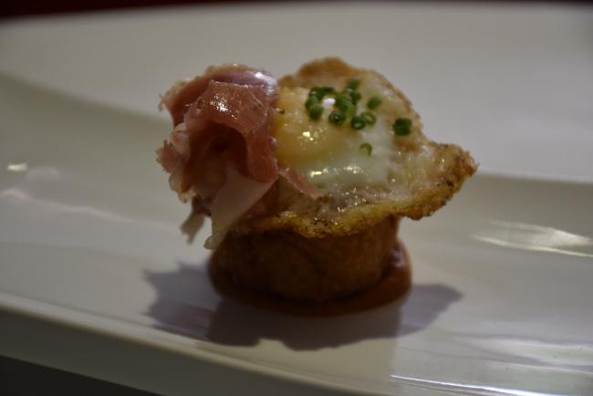 Buñuelo de bacalao con base de verduras asadas, huevo de codorniz y jamón ibérico