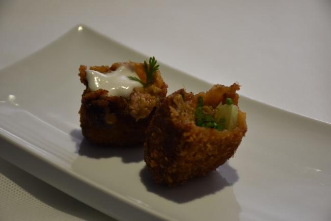 Croquetas de pollo al curry rojo tahilandés en dos bocados, uno con coco y otro con lima