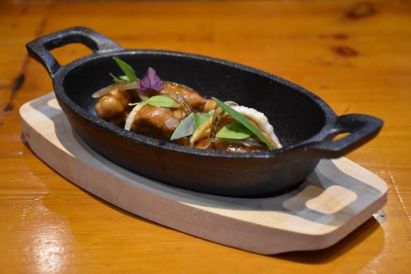 Molleja glaseada con americana picante, hojas de curry y cebolla